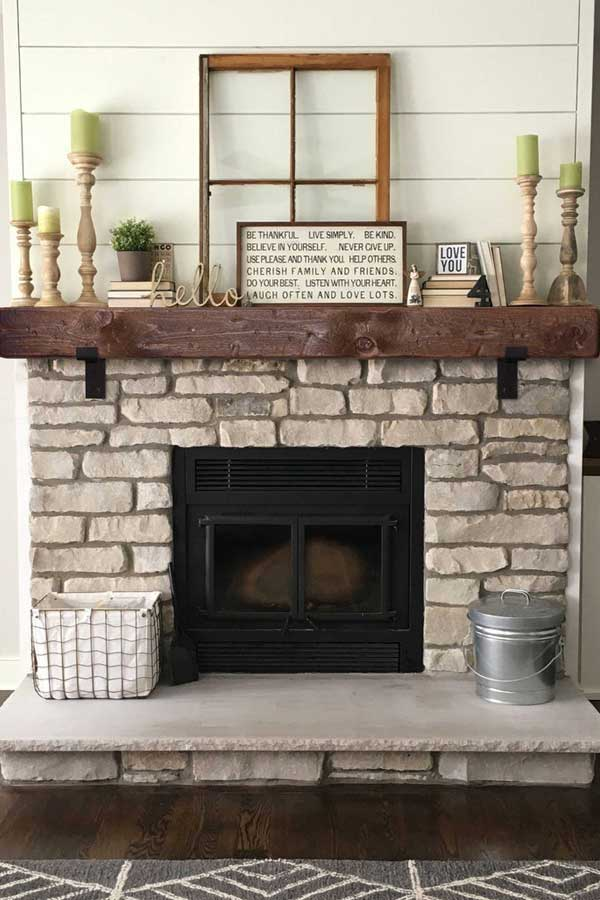 A well-decorated fireplace mantel with focal point, greenery, and candlesticks